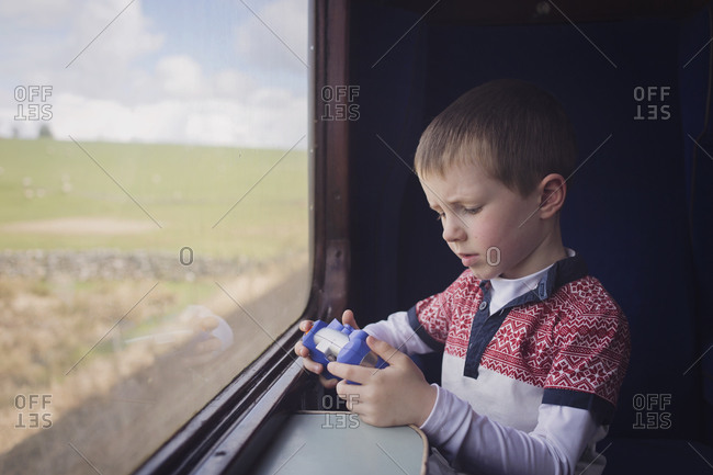 A boy plays with a toy on a train