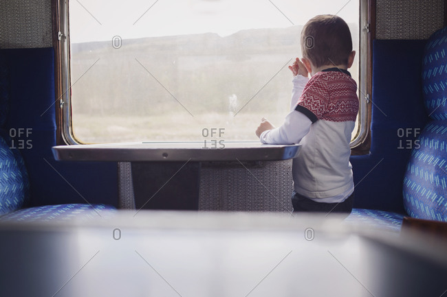 A boy looks out the window of a train