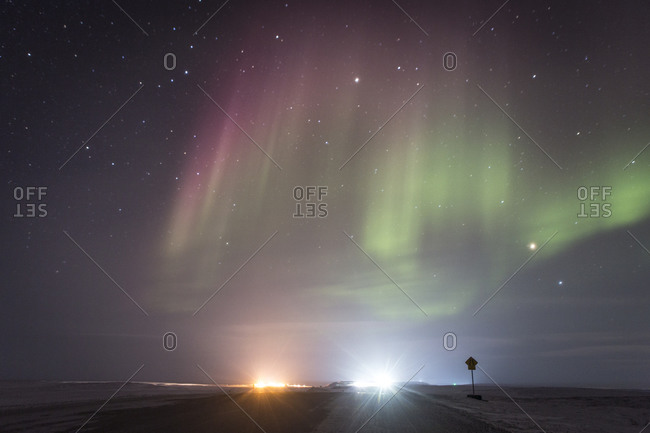 Shimmering pink and green Northern lights over distant town