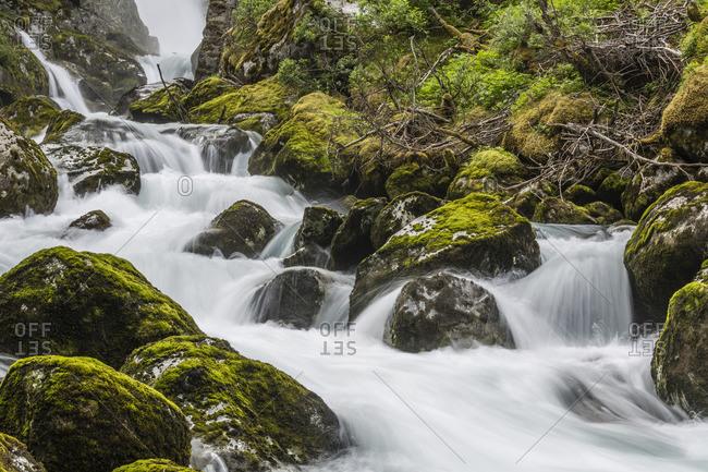 Silky water of the Olden River as it flows along Briksdalen, Olden, Nordfjord, Norway, Scandinavia