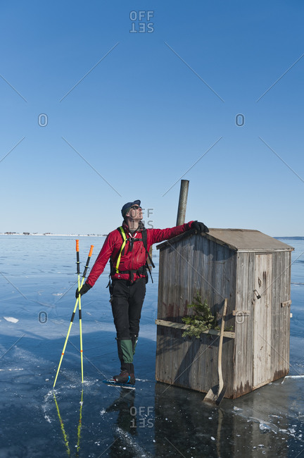 Ice-skater standing near shed - Offset