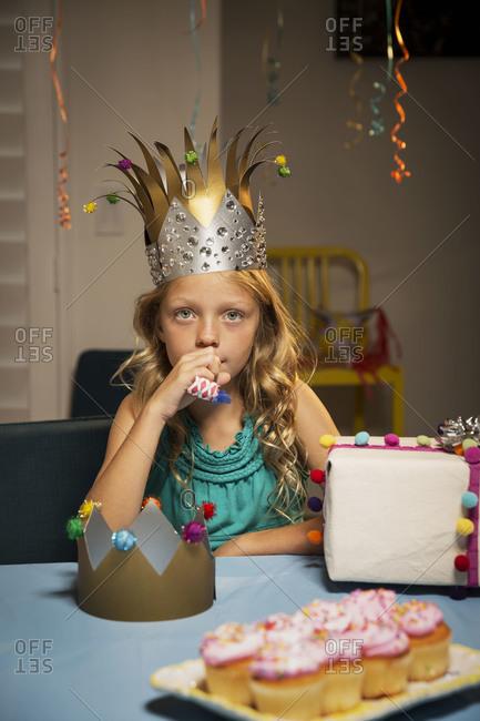 Girl holding noisemaker at table