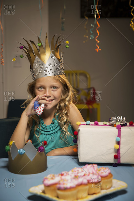 Smiling girl with noisemaker and cupcakes