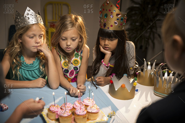 Children at birthday party watch candles being lighted