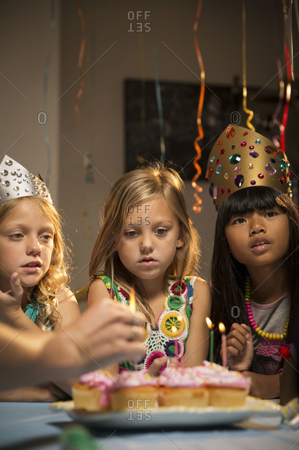 Three girls watch candles being lighted at party