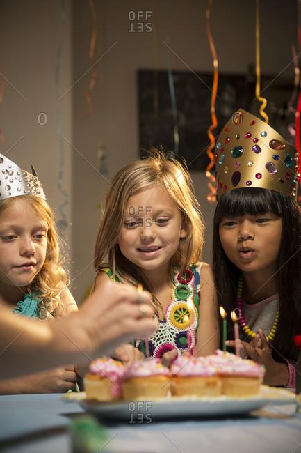 Three girls watching cupcake candles being lit