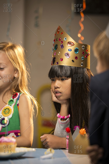 Girl looking at candles on birthday cupcakes
