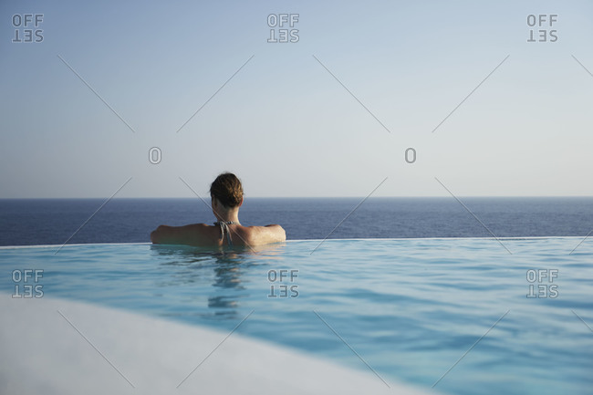 Woman relaxing in an infinity pool