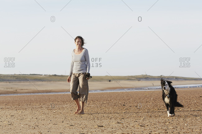 Woman with her dog on a beach