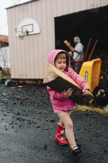 Little girl carrying a log