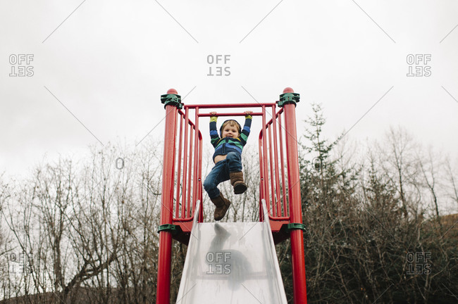 Young girl hanging on a sliding board