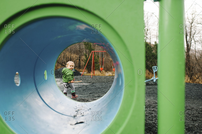 Young girl looking through a tunnel on a playground