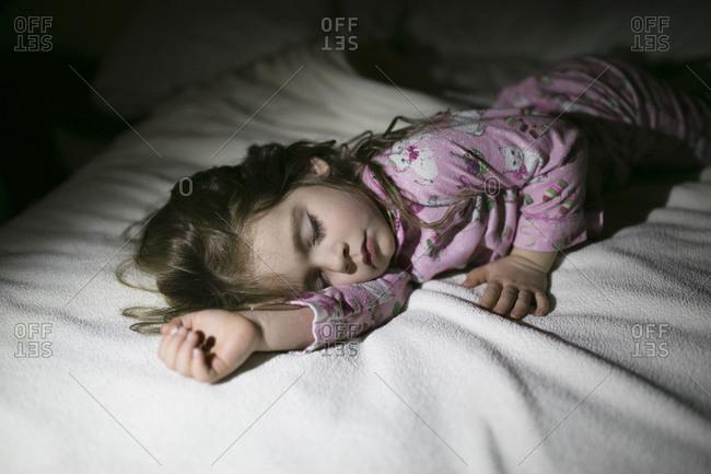 Little girl in pajamas asleep on bed