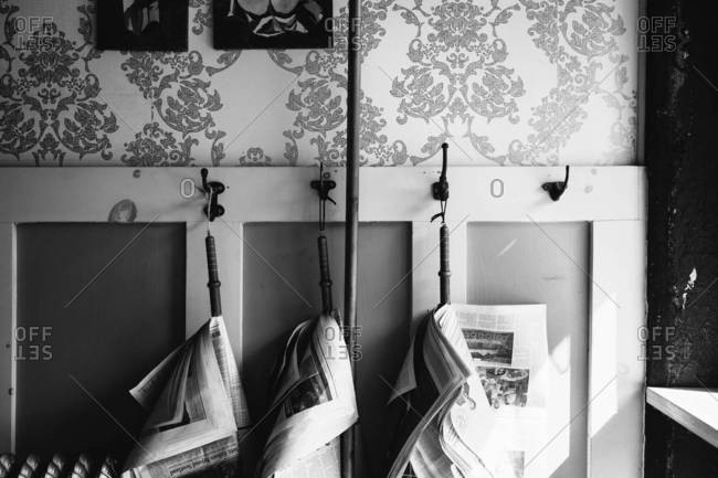 Newspapers hang from rods