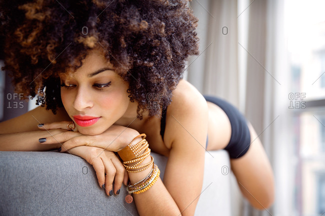 A woman lies on the top of a couch