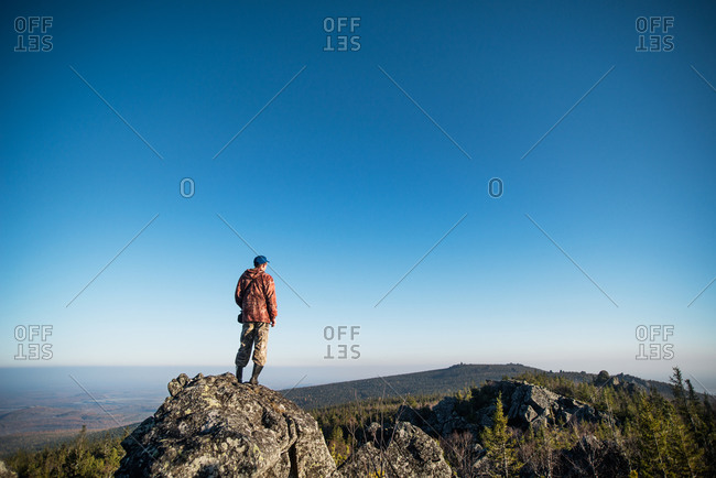 Man standing and watching the landscape from a rock