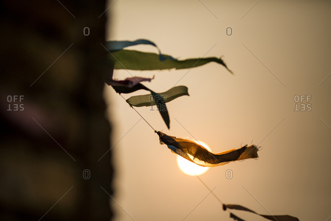 Prayer flags flutter as the sun sets in the distance in Xieng Khouang province, Laos
