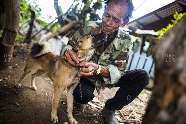 Sakon Nakhon, Thailand - September 2, 2014: Man plays with his pet dog outside of his home