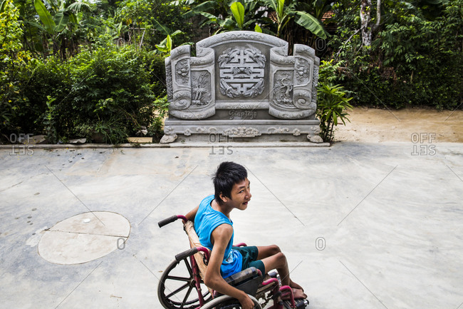 Quang Tri, Vietnam - September 10, 2014: A young wheelchair-bound man in Quang Tri Province, Vietnam whose ailments are thought to be from his mother and father's exposure to Agent Orange during the Vietnam-American War