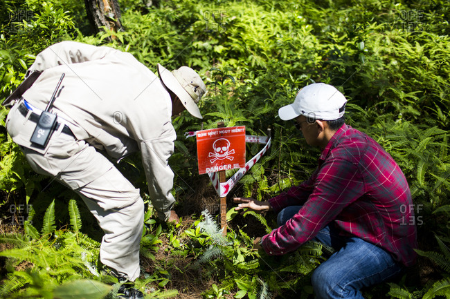 Vinh An Village, Quang Tri, Vietnam - September 10, 2014: Members of the Project Renew searching for mines in a heavily forested area in Quang Tri Province, central Vietnam