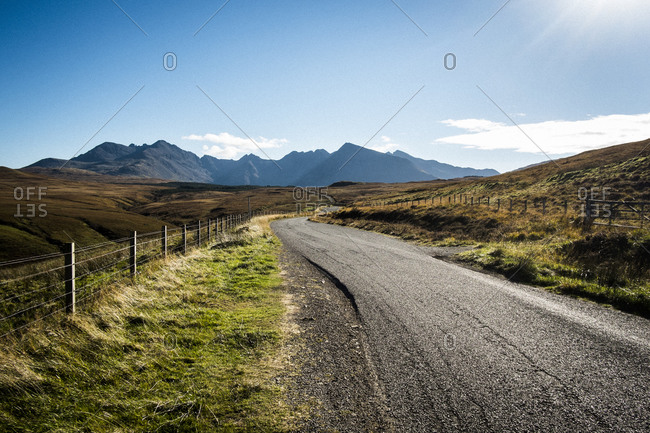 A lonely road cuts through a mountainous landscape in the western highlands of Scotland