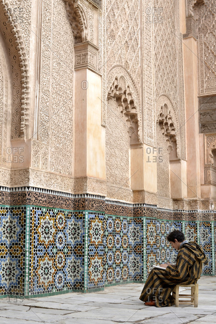 Marrakesh, Morocco - November 24, 2014: Man drawing in the courtyard of Ben Youssef Madrasa