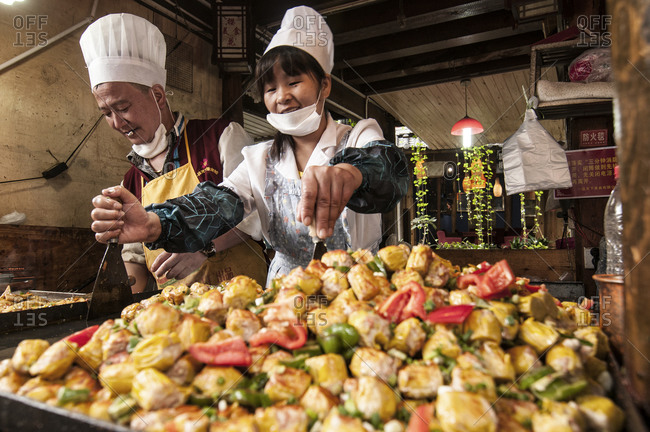 Lijiang, China - August 10, 2013: Workers in a food stall