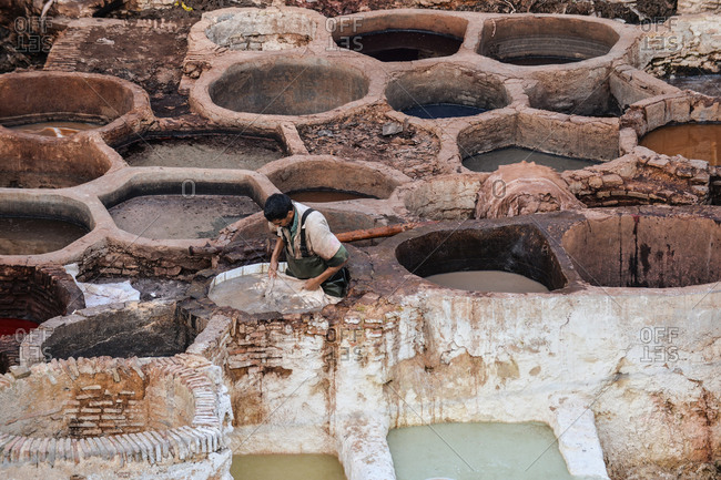 Fez, Morocco - November 18, 2014: Person dyeing leather in a tannery