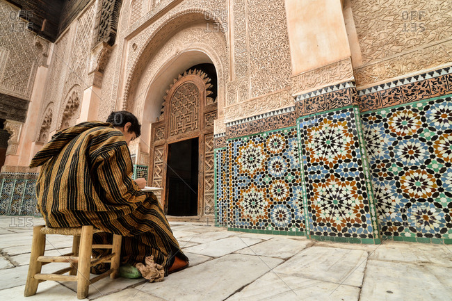 Marrakesh, Morocco - November 24, 2014: Man sketching in the courtyard of Ben Youssef Madrasa