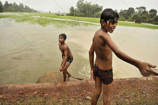 Angkor, Cambodia - September 17, 2012: Boys bathing in a lake