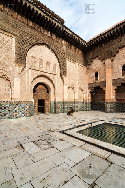 Man sitting in the courtyard of Ben Youssef Madrasa