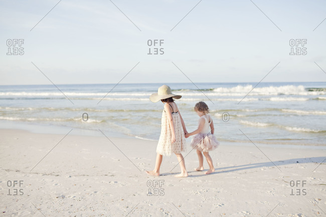 Siblings holding hand on beach