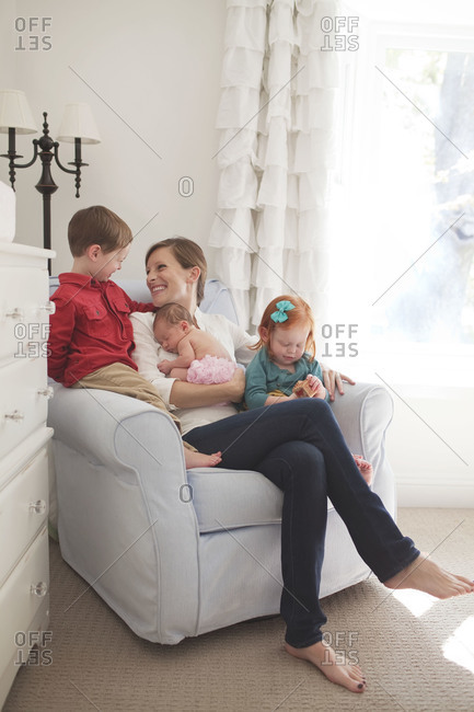 Mother sitting in armchair with children