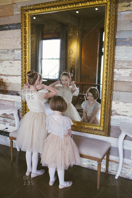 Young girls adjusting outfit in front of mirror