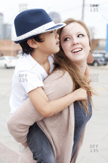 Young woman carrying boy