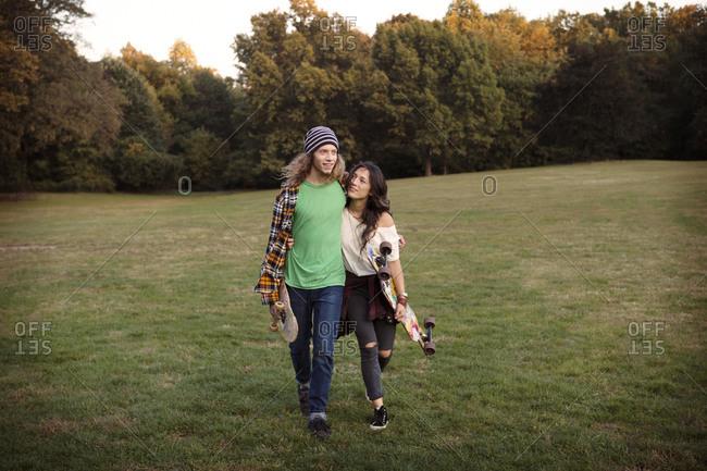 Skater couple walking in park
