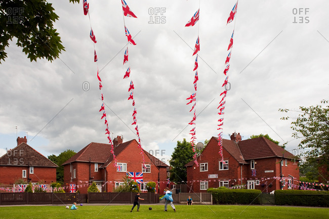 Manchester, UK - June 4, 2012: Children playing soccer under English flags