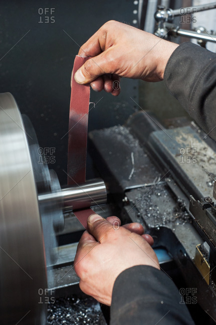 Man cleaning metal tube with sandpaper