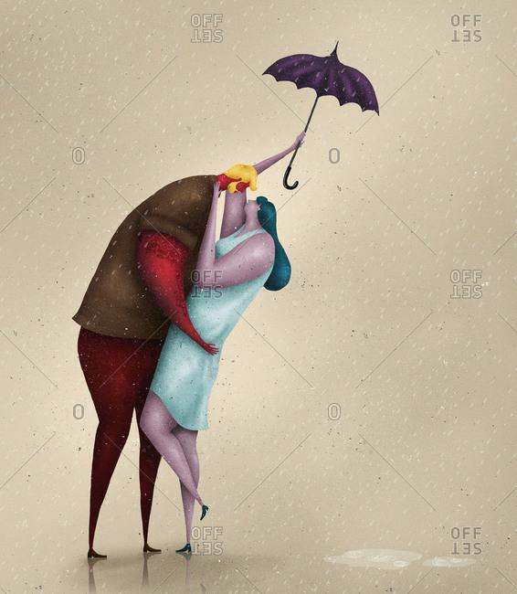 Couple hugging under an umbrella in the rain