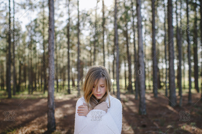 Girl standing in forest covered with blanket