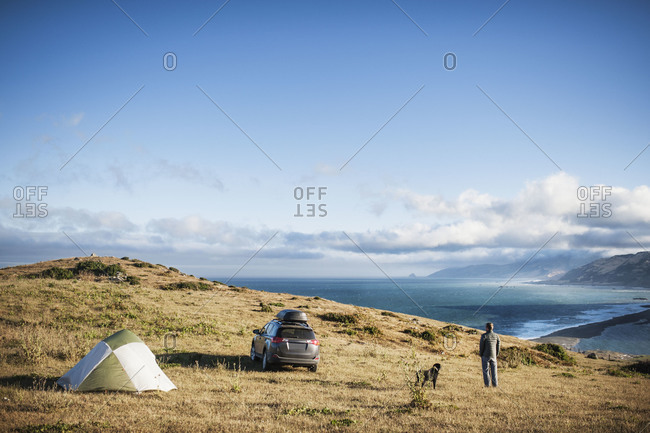 Man camping with dog - Offset