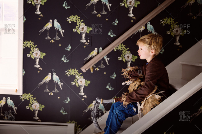 A boy sits on a staircase