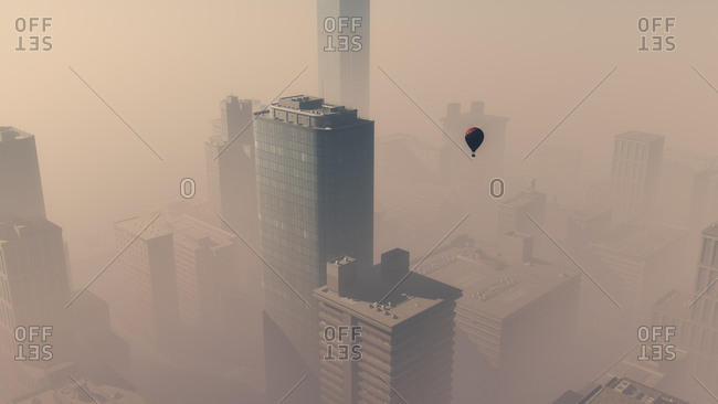 Aerial of hot air balloon flying over skyscraper city in the mist