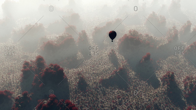 Aerial of hot air balloon flying over mountain landscape with red trees
