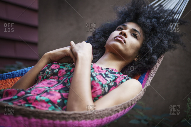 Pensive woman lying in hammock