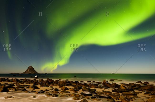 Aurora Borealis glimmering over beach
