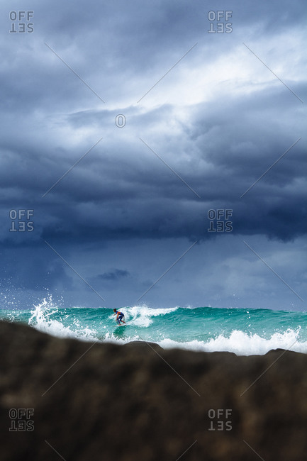 Burleigh Heads, Queensland, Australia - June 9, 2014: Surfer outside Burleigh Heads catching a wave