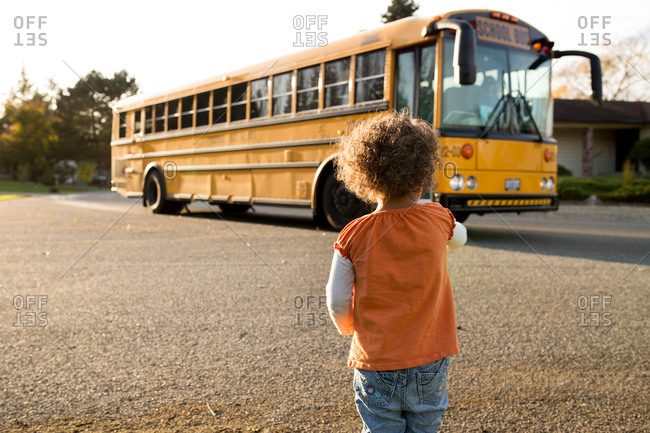 Small child watching school bus