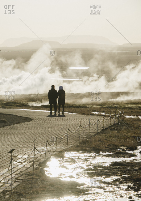 Couple walking along geysers in Iceland