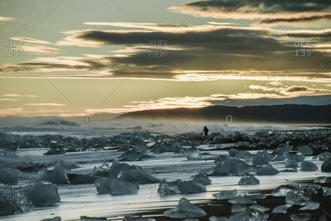 Photographer with ice chunks on an Icelandic coast
